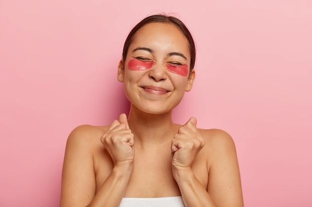 Dolblij etnische vrouw balt vuisten met triomf, geniet van dagelijkse verwenningsroutine, verzorgt de huid, gebruikt ooglapjes, sluit de ogen van genot tijdens schoonheidsbehandelingen, poseert binnen Gratis Foto