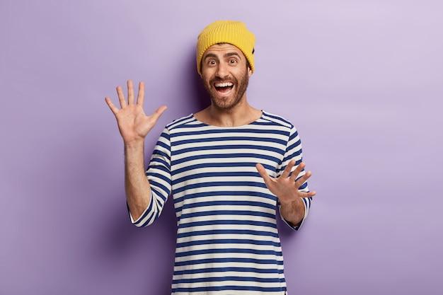 Dolblij ongeschoren duizendjarige man gebaart actief, toont palmen, is in goed humeur, draagt een gele hoed en gestreepte trui Gratis Foto