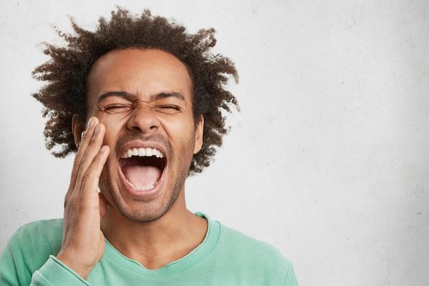 Dolblij opgewonden gelukkig gemengd ras man opent mond wijd, sluit ogen, schreeuwt vreugdevol Gratis Foto
