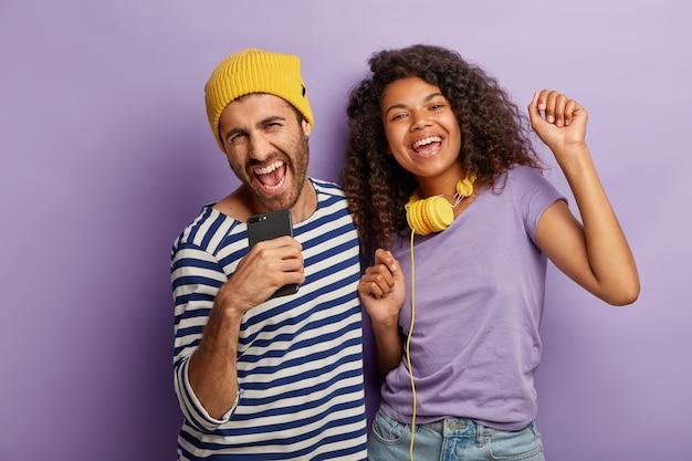 Dolgelukkig gemengd ras duizendjarige vrouw en man hebben samen plezier, zingen luid en dansen op muziek, gebruiken moderne technologieën voor entertainment Gratis Foto
