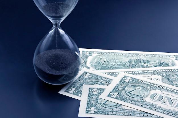 Dollarbiljetten liggen bij de zandloper. tijd is geld Premium Foto