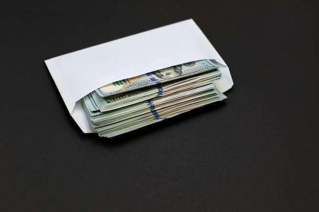 Dollargeld in de envelop op zwarte achtergrondbonus, beloning, voordelenconcept. Premium Foto