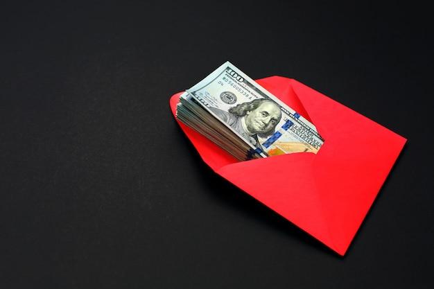 Dollargeld in de rode envelop op zwarte Premium Foto