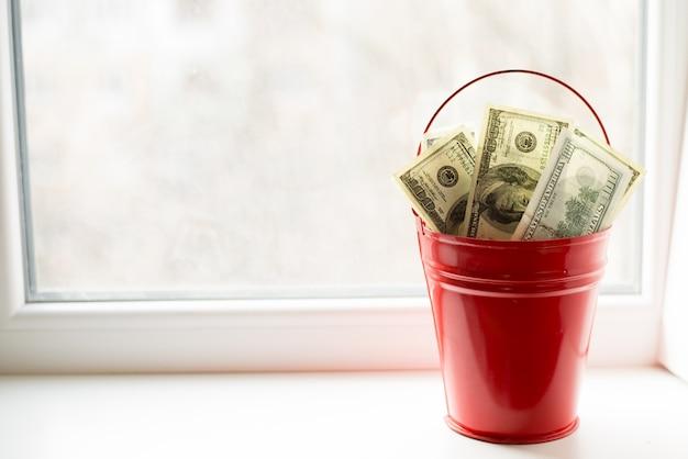 Dollarrekeningen in rode emmer. op witte window.light achtergrond. Premium Foto