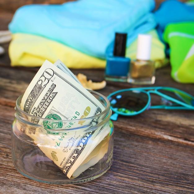 Dollars in glazen pot. concept van het verzamelen van geld voor de reis. Premium Foto