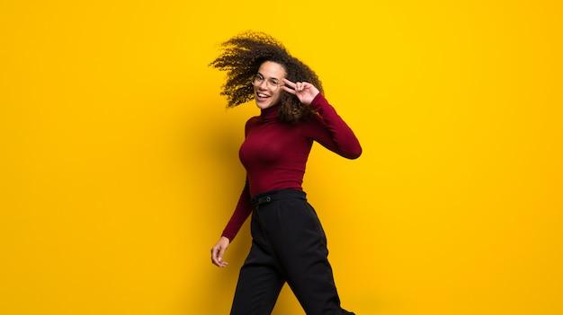 Dominicaanse vrouw die met krullend haar op gele muur springt Premium Foto