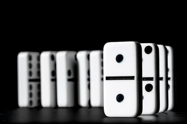 Domino's die zich op een rij op zwarte achtergrond bevinden Premium Foto