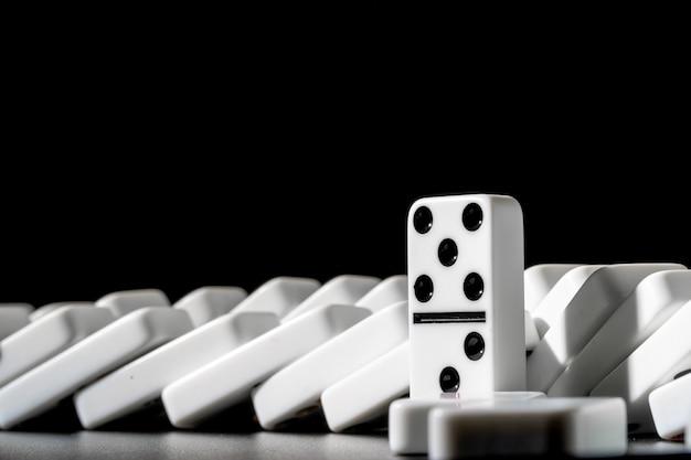 Domino's die zich op een rij op zwarte bevinden Premium Foto