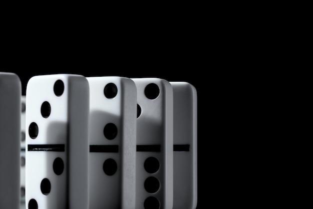 Domino's die zich op een rij op zwarte muur bevinden Premium Foto