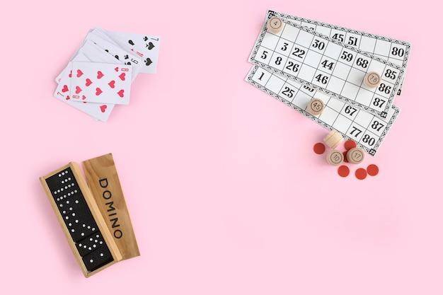 Domino, speelkaarten en lotto op roze muur, bovenaanzicht. bordspellen voor familie Premium Foto