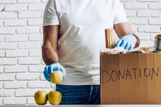 Donatiebox met voedsel voor mensen die lijden aan de gevolgen van coronavirus en pandemie Premium Foto
