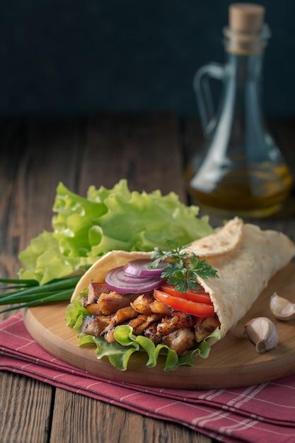 Doner kebab ligt op de snijplank. shoarma met kippenvlees, uien, salade ligt op een donkere oude houten tafel. Premium Foto