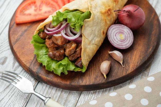 Doner kebab ligt op de snijplank. shoarma met vlees, uien, salade ligt op een donkere oude houten tafel. Premium Foto