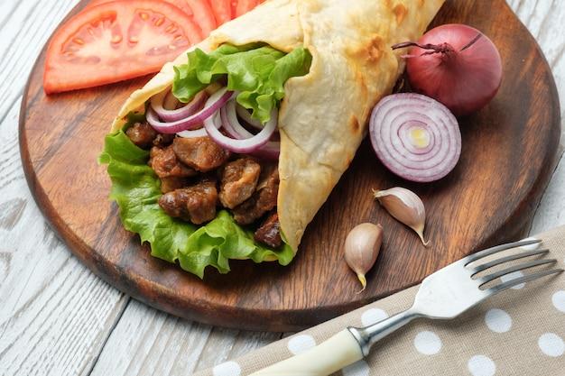 Doner kebab ligt op de snijplank. shoarma met vlees, uien, salade ligt op een witte oude houten tafel. Premium Foto