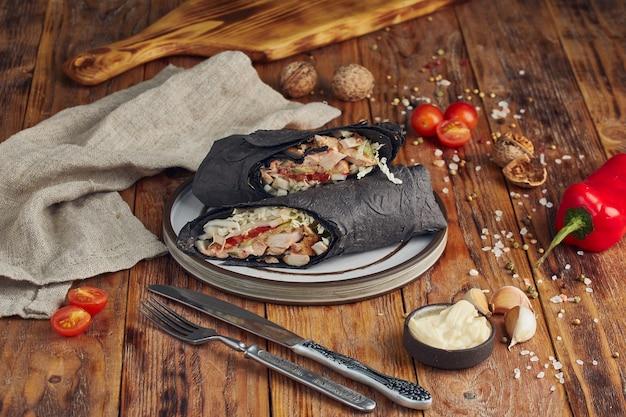 Döner kebab (shoarma of döner wrap). gegrilde kip op lavash met tomaten, groene salade en paprika op de houten tafel Premium Foto