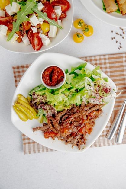 Doner segmenten met groene salade en uien op een witte plaat Gratis Foto