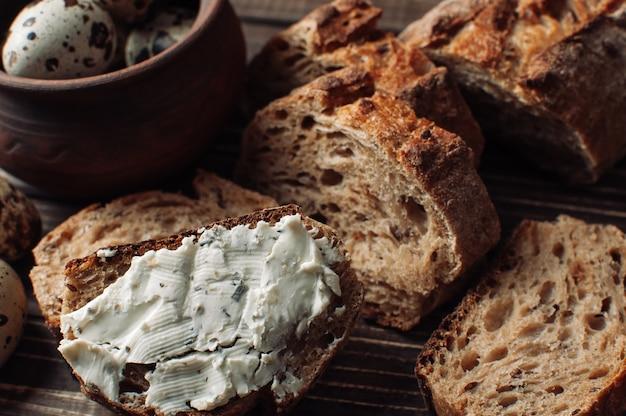 Donker boekweitbrood wordt verspreid met kwark met kruiden in een snee op een houten tafel in de buurt van kwartelseieren in een kleiplaat in een rustieke stijl. Premium Foto
