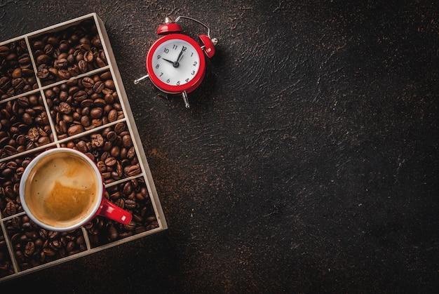 Donker oppervlak met koffiebonen, een wekker en een kopje koffie Premium Foto