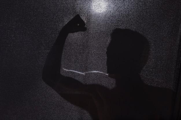 Donker silhouet van kerel die bicepsen toont Gratis Foto
