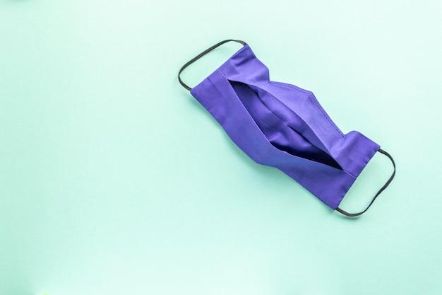 Donkerblauw herbruikbaar masker op een mint effen achtergrond. plaats voor tekst. geneeskunde. Premium Foto