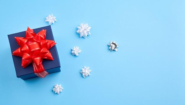 Donkerblauwe kartonnen geschenk vierkante doos, rode strik, linten op een blauwe achtergrond Premium Foto