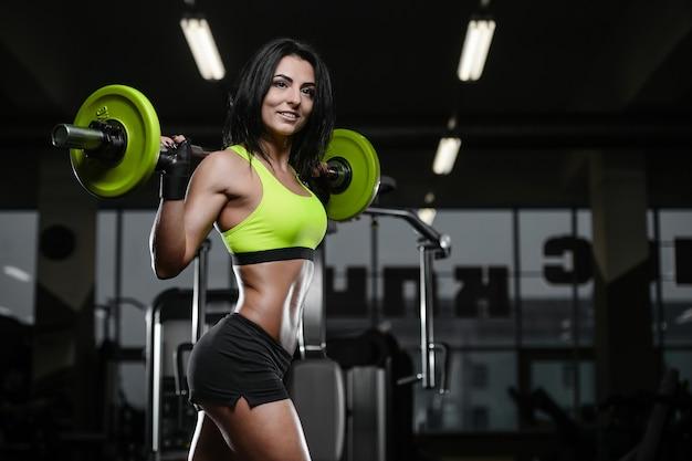 Donkerbruin atletisch jong meisje dat in gymnastiek uitwerkt Premium Foto