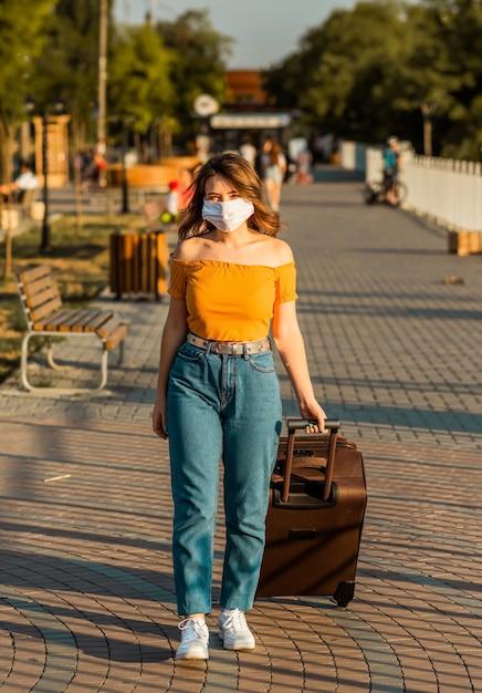 Donkerbruin meisje dat een chirurgisch masker draagt, loopt in park met haar koffer. Premium Foto