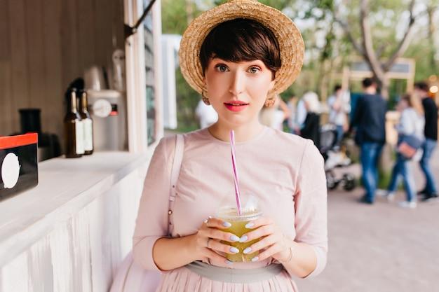 Donkerbruin meisje in strohoed die zich met verbaasd de holdingsglas van de gezichtsuitdrukking van groene cocktail bevinden Gratis Foto