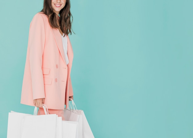 Donkerbruine dame in roze kostuum met winkelnetten Gratis Foto