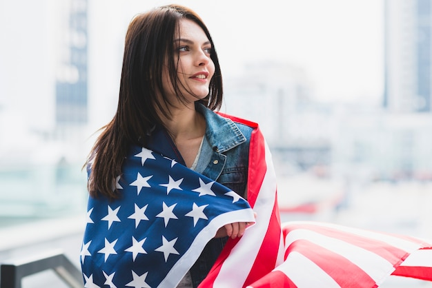 Donkerbruine die vrouw in amerikaanse vlag op achtergrond van stad wordt verpakt Gratis Foto