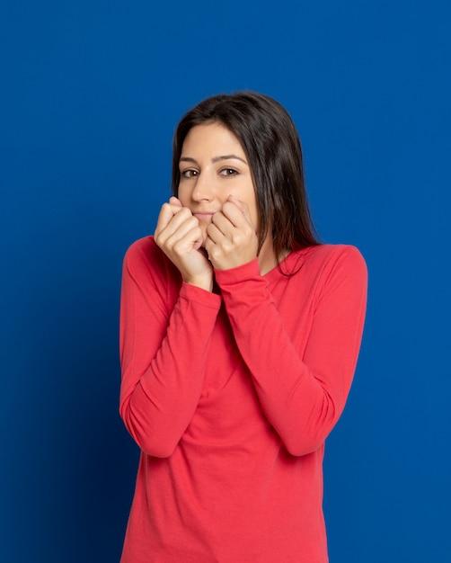 Donkerbruine jonge vrouw die over blauwe muur gesturing Premium Foto