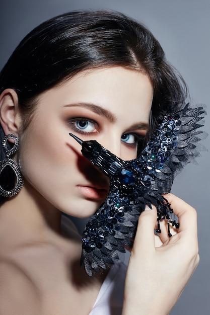 Donkerbruine meisjes blauwe ogen die zwarte brocheavogel houden Premium Foto
