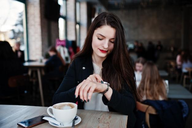 Donkerbruine meisjeszitting op koffie met kop van cappuccino en het bekijken haar horloges bij de hand. Premium Foto