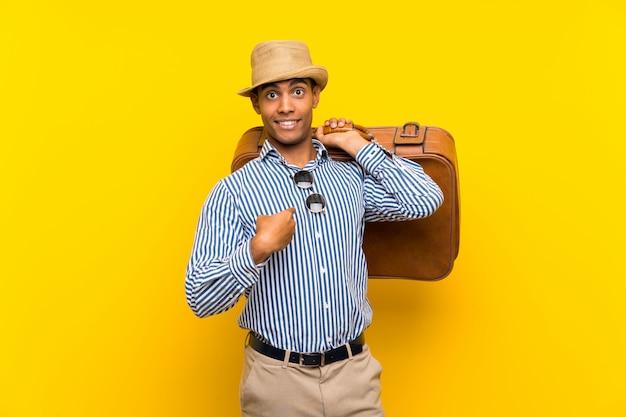 Donkerbruine mens die een uitstekende aktentas over geïsoleerde geel met verrassingsgelaatsuitdrukking houdt Premium Foto