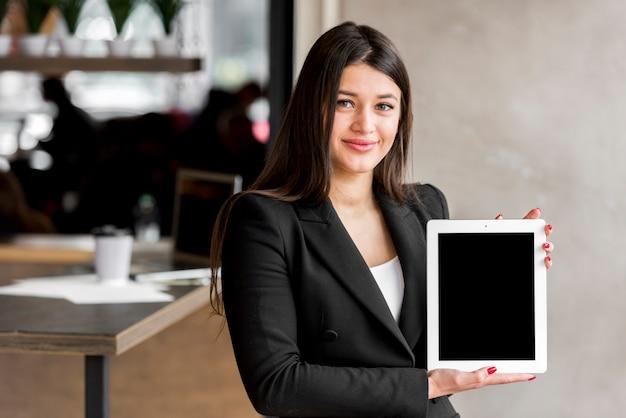 Donkerbruine onderneemster die een tablet toont Gratis Foto