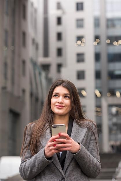Donkerbruine onderneemster die haar smartphone gebruikt Gratis Foto