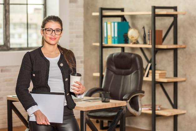 Donkerbruine onderneemster op haar kantoor Gratis Foto