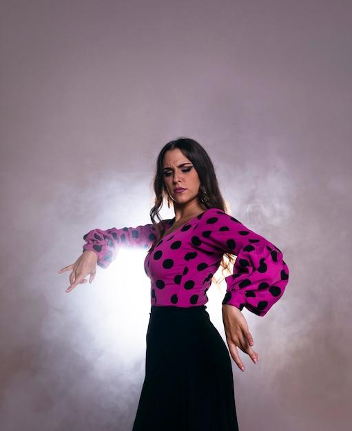 Donkerbruine vrouw die met licht op de rug danst Gratis Foto