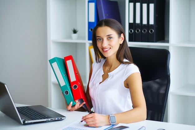 Donkerbruine vrouw die telefoon bekijkt terwijl het werken Premium Foto