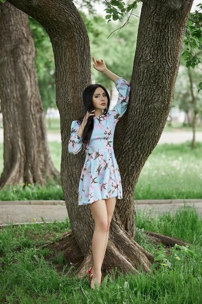 Donkerbruine vrouw in de takken van een mooie bloeiende boom. Premium Foto