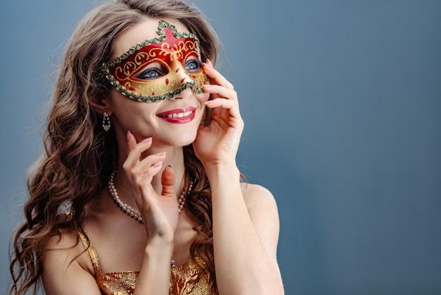 Donkerbruine vrouw in een kleurrijk carnaval-masker op een blauwe achtergrond die en omhoog glimlacht kijkt Premium Foto