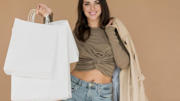 Donkerbruine vrouw met laag op schouder en het winkelen zakken Gratis Foto