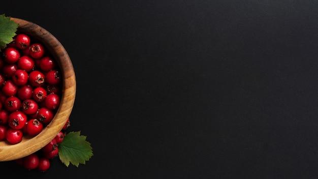 Donkere banner met bessen in houten kom. Premium Foto