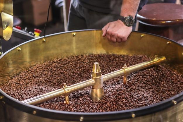 Donkere en aromatische koffiebonen in een moderne braadmachine Premium Foto