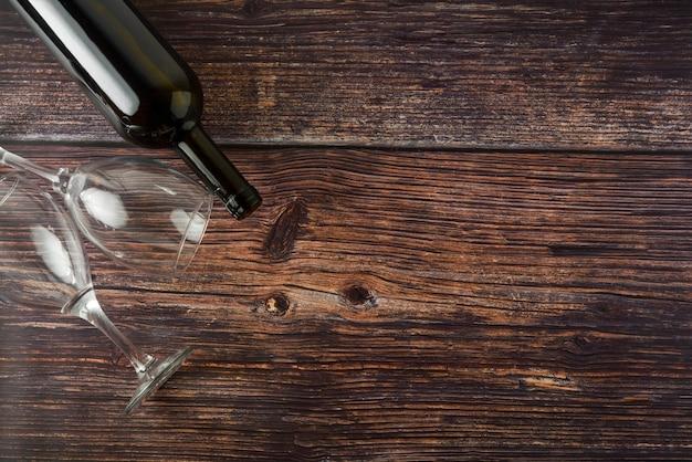 Donkere fles wijn en glazen op houten achtergrond. bovenaanzicht met kopie ruimte. Premium Foto