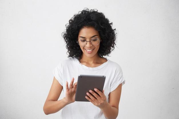 Donkere glimlachende charismatische en mooie vrouwelijke student die moderne gadget vasthoudt, tablet gebruikt voor een videogesprek met haar vrienden, grappige video's bekijkt of huiswerk maakt, chatten Gratis Foto