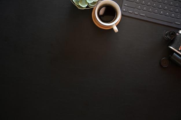 Donkere het bureaulijst van de leerbureau fotografie met toetsenbordtablet en uitstekende camera Premium Foto