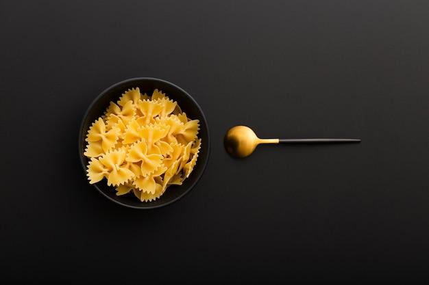 Donkere kom met pasta en lepel op een donkere tafel Gratis Foto