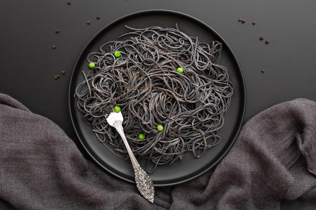 Donkere pasta plaat op een donkere doek Gratis Foto