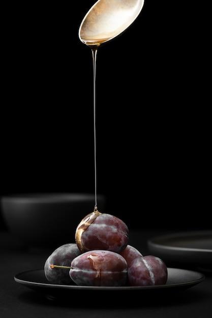 Donkere plaat met pruimen op een donkere achtergrond Gratis Foto